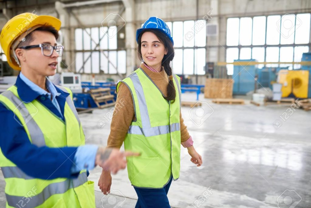 A non-binary person in a hardhat, walking beside a woman in a hardhat.
