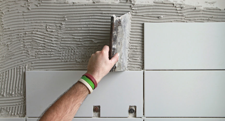 A hand applying bathroom tile.