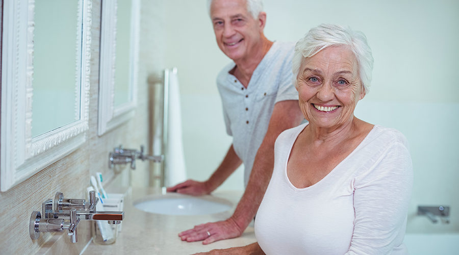 An elderly couple standing together at their bathroom sink, looking directly into the camera and smiling.